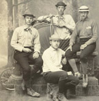 The Amherst Bicycle Club in Brattleboro, Vermont on May 16, 1881. Portrait of four club members taken in the Brattleboro studio of C. L. Howe. Members are wearing athletic clothes of the day and posed with a high wheeler bicycle. Item #747