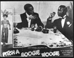 Postcard showing actors Tom Foreman and Herman Forbes seated at a table in the dream night club, in a still from the 1948 movie Pitch a Boogie Woogie. The film was the only commercial production by North Carolina's first movie company, Lord-Warner Productions and was produced with an all-black cast of primarily local performers.