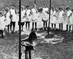 Toothbrush Drill at the Brackenridge School, Houston. 	Printed half-tone photograph of a group of unidentified children at the Brackenridge School standing in a semi-circle and participating in a toothbrush drill, 1914-1915. An early phonograph with external horn is in the foreground. A horse and carriage are stopped in an unidentified street in the background.
