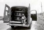 A girl reads in the back of the Tyrrell County (N.C.) Public Library bookmobile, 1930s